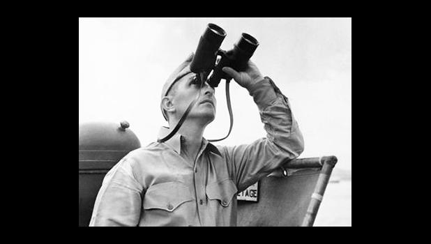 This October 1942 file photo shows Eugene Burns, Associated Press war correspondent with the Pacific Fleet, on the deck of a Navy vessel with binoculars raised as he covered operations of a task force in the South Pacific. On Dec. 7, 1941, as Japanese bombs rained down on Pearl Harbor, Burns, Associated Press chief of bureau in Honolulu, was unable to get out the urgent news of the historic attack that would draw the U.S. into World War II. The military had already taken control of all communication lines,