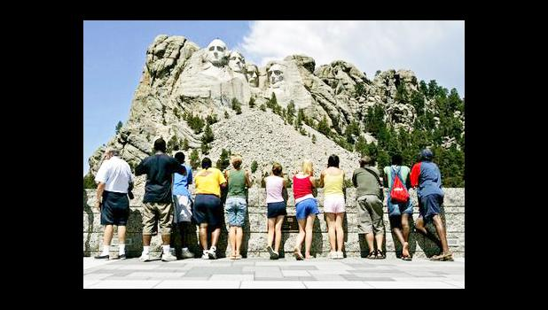 """n this July 21, 2005 file photo, visitors watch while workers pressure wash the granite faces of George Washington, left, Thomas Jefferson, Theodore Roosevelt and Abraham Lincoln at Mount Rushmore National Memorial in South Dakota. The Democracy Index, compiled by the London-based Economist Intelligence Unit, ranked the U.S. at 21st worldwide in 2016, tied with Italy and trailing Norway, Canada and Uruguay, among others. While Norway and several other Scandinavian countries are considered """"full democracies,"""
