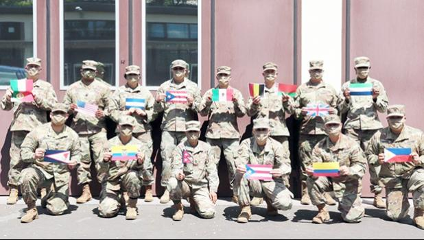 Diverse members of 773rd Civil Support Team, wih flags of their countries of origin.