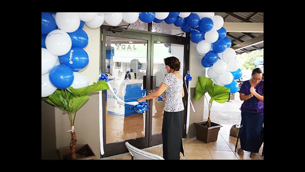 Human Resources Manager Jeannette Yamasaki – one of the longest working employees at Bluesky Communications cutting the ribbon to officially open their newly renovated store, on the ground floor of the Laufou Shopping Center yesterday morning, which also recognized Mrs. Yamasaki's dedication and service to the company. [photo: TG]