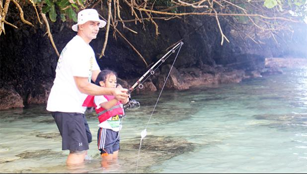 One of the youngest participants in this year's Sanctuary Summer Science in the Village (SSSV) program, learning how to properly use a fishing pole during one of four Tautai Fagota Fishing Derbies  hosted by the NMSAS and local sponsor SOPAC/Aloha Maid.  [photo: BC]