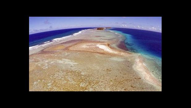 In this Nov. 5, 2015 file, aerial photo a small uninhabited island that has slipped beneath the water line only showing a small pile of rocks at low tide on Majuro Atoll in the Marshall Islands. To small island nations where the land juts just above the rising seas, the U.S. pulling out of the Paris global warming pact makes the future seem as fragile and built on hope as a sand castle. [AP file photo]