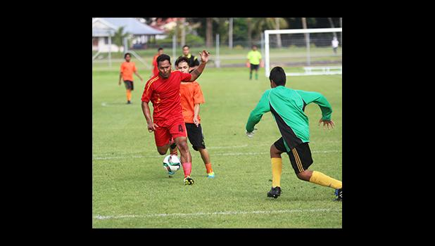 Iosia Tasi of Black Roses defends against a Royal Puma attacker to give his goalie time to collect the ball during a men's game on Match Day 4 of the 2016 FFAS National League on Saturday, Sept. 10, at Pago Park Soccer Stadium.  [FFAS MEDIA/Brian Vitolio]