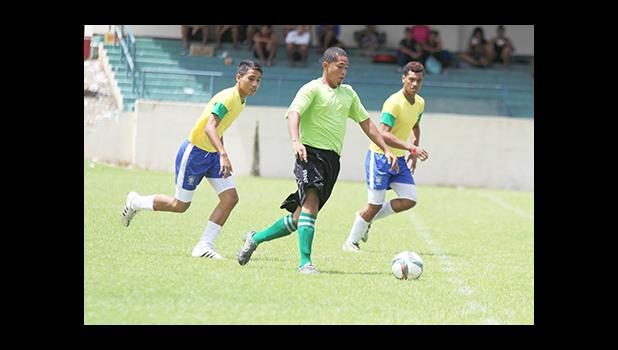 A Lion Heart player dribbles away from Vaiala Tongan opponents on in a men's game on Match Day 12 of the ongoing, 2016 FFAS National League on Saturday, Nov. 12, at Pago Park Soccer Stadium.  [FFAS MEDIA/Brian Vitolio]