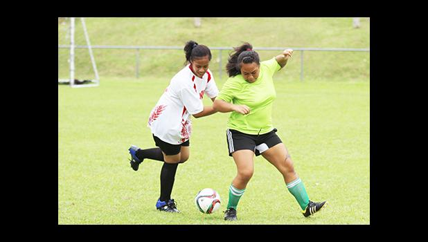 A Vaiala Tongan player (left) and Lion Heart opponent fight for possession of the ball during a women's game on Match Day 5 of the 2016 FFAS National League on Saturday, Sept. 17, at Pago Park Soccer Stadium. [FFAS MEDIA/Brian Vitolio]