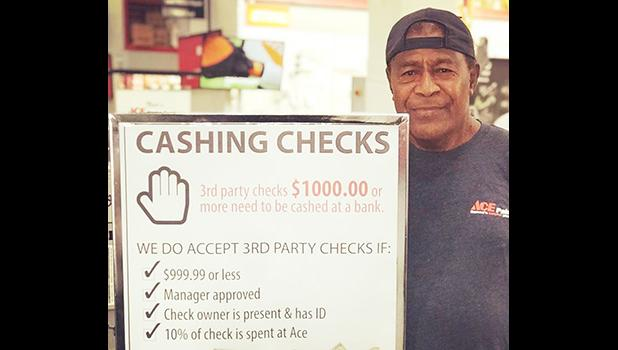 ACE employee beside their check chasing policy sign