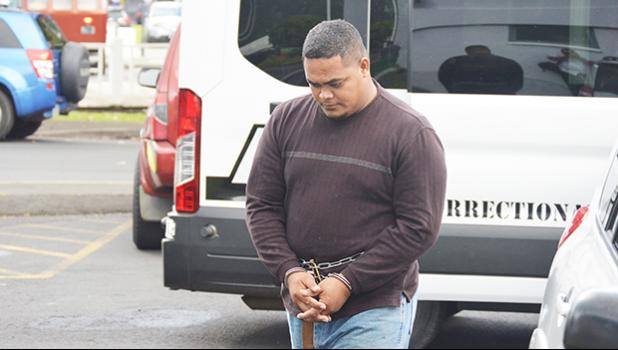 Amosa Lautaimi, handcuffed and making his way to the District Court yesterday morning for his initial appearance