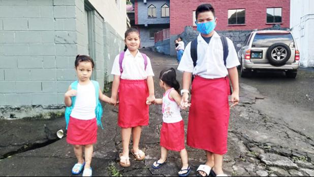 Matafao Elementary School students holding hands on their way to school