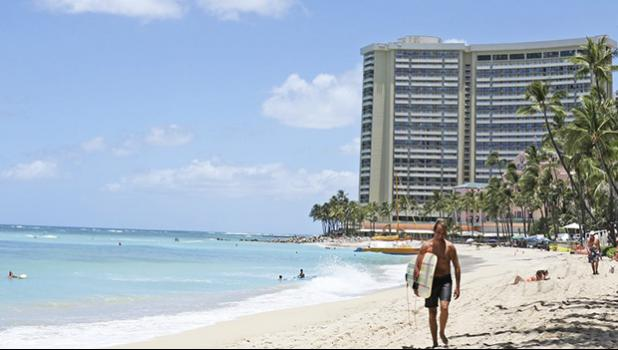 Man walking on Waikiki beach with hotel in the background.