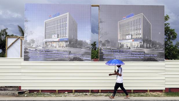 a man walks past a development site for a Chinese Investment bank in Nuku'alofa, Tonga