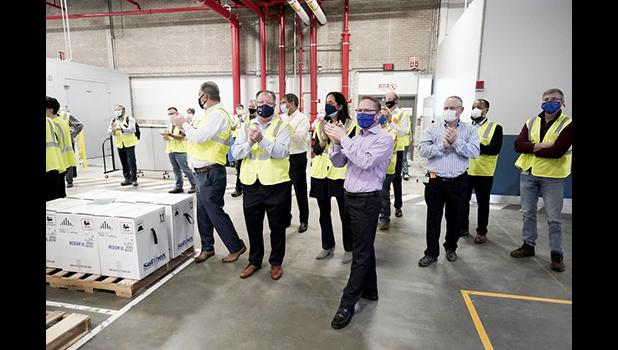 Pfizer employees clap after line workers finished packing boxes of vaccine