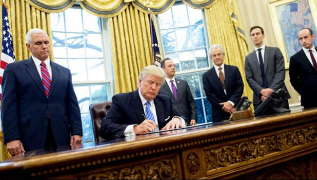 Donald Trump, seated, signed, three executive orders on Monday, including one banning any US-funded organisations from speaking about abortion. [Photo: AFP via RNZI]