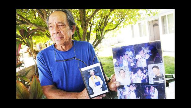"""In this Monday, July 10, 2017 photo, Clifford Kang, father of soldier Ikaika E. Kang, poses with photo of his son in Kailua, Hawaii. Ikaika E. Kang, an active-duty U.S. soldier, was arrested over the weekend on terrorism charges that accuse him of pledging allegiance to the Islamic State group and saying he wanted to """"kill a bunch of people."""" (Bruce Asato/The Star-Advertiser via AP)"""