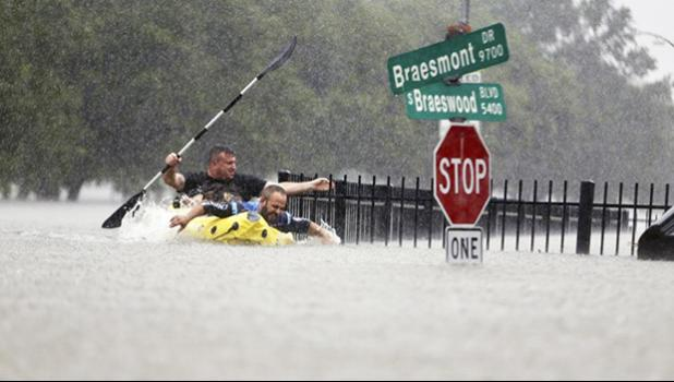 Flooding in Houston with two men paddling in the water