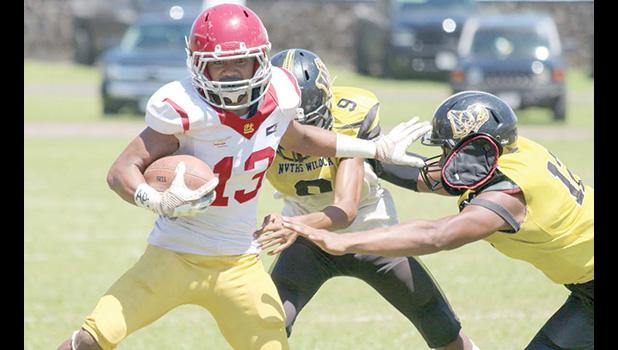 Tafuna's ball carrier trying to evade the pressure from two Nu'uuli Wildcat defenders