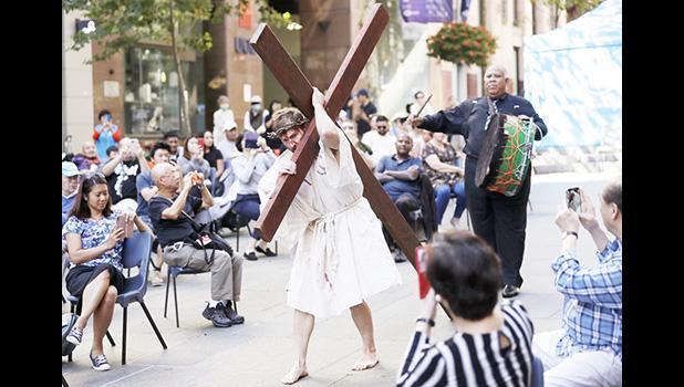 Actor Timothy Watkins carries a cross