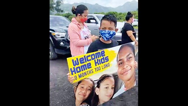 Young boy holding welcome banner