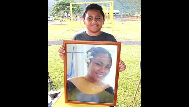 Eleven-year-old Malakai, posing for Samoa News with a portrait of his mother, Sabrina Seva'aetasi