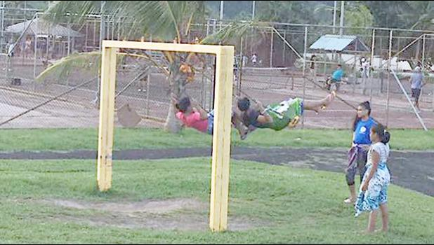 Children swinging on playground equipment at Lions Park