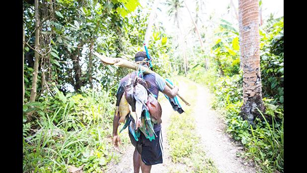 Man walking through the bush with a string of fish over his sholder
