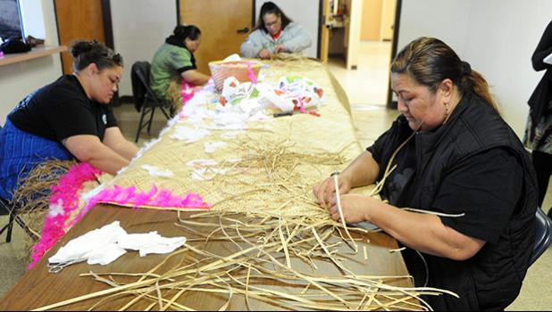 Felolins Mawong, left, and Tauva Filivaa, front, work with Sopa Saina, back left, and Falesoa Iaulalo on a mat for a family who lost a loved one. [Calixtro Romias / The Record]