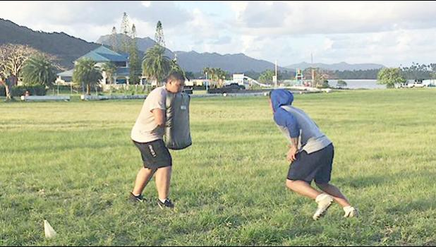 Two high school football players working out