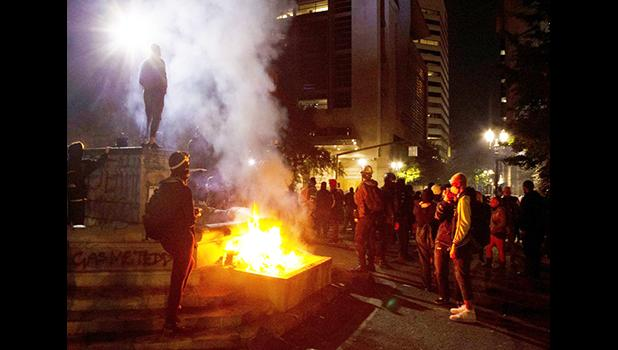In this July 4, 2020, file photo, protesters gather near a fire in downtown Portland, Ore