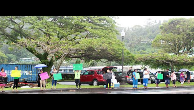 """A group of residents - some with umbrellas - participating  in the """"Wave for repatriation flights - Not open borders"""""""