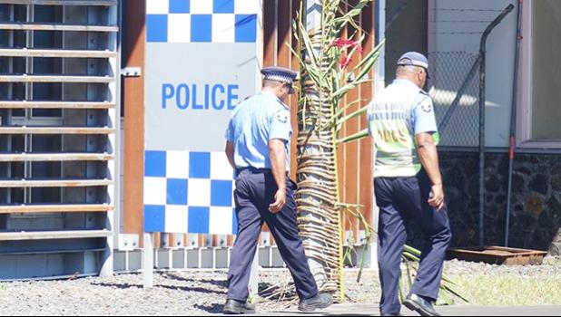 Two police officers walking out of police headquarters in Apia