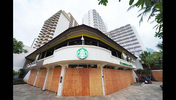 A Waikiki Starbucks coffee shop near Kapahulu Avenue with windows boarded up