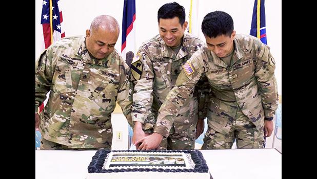 Staff Sgt. Faiupu Tagaleoo, assigned to Theater Support Group American Samoa Detachment, 9th Mission Support Command (left), representing the oldest unit member, and Pvt. Vend Luafutu, assigned to Charlie Company, 100th Battalion, 442nd Infantry Regiment, 9th Mission Support Command (right), along with Lt. Col. Alejandro Buniag, Commander, Theater Support Group American Samoa Detachment