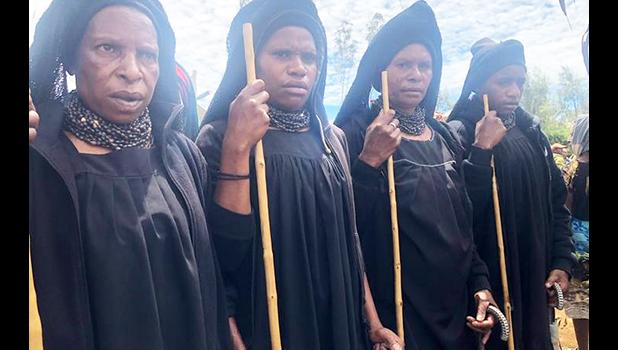 Highlands women dressed in long black robes attending a funeral