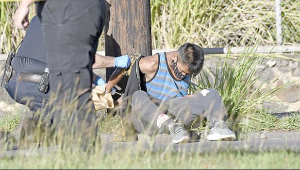 robbery suspect sitting in grass being handcuffed