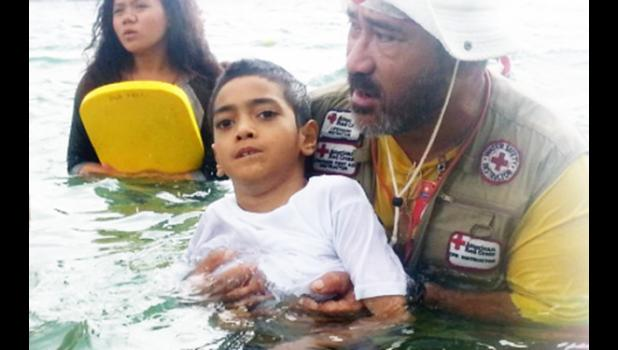 Swimming Coach, Zero Iaulualo with a special needs child during their swimming lessons in 2015 in conjunction with parents' group PCSN Network.