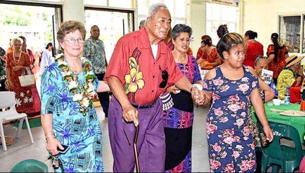 Evelyn Lili'o Satele (left) helps escort an elderly member of the community