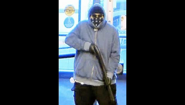 Totoe Opeti Sakaria, Jr., who is masked, wearing sunglasses and holding a shotgun