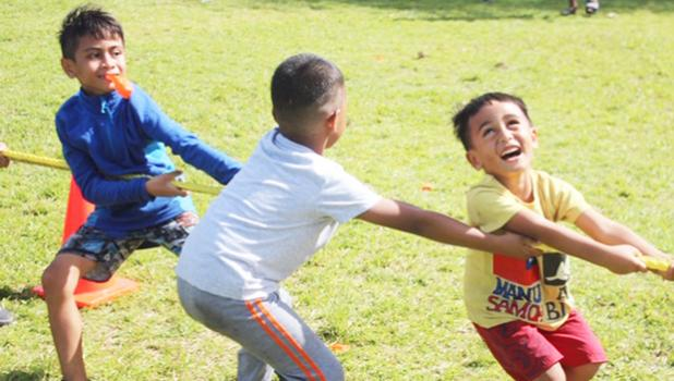 Three youngsters really enjoying themselves during the tug-of-war