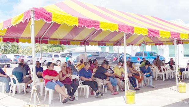 Individuals waiting under a tent next to the DoH quarantine facility