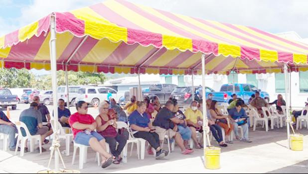 Individuals waiting to get their COVID-19 vaccine under a tent next to the DoH quarantine facility in Tafuna