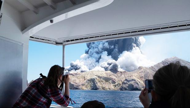 Tourists on a boat look at the eruption of the volcano