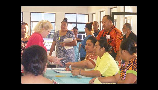 A registered voter (left) speaking to election officials seconds after the polling station at Ili'ili opened at 6a.m. today.  [photo: Fili Sagapolutele]