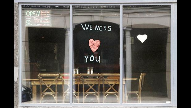 "Sign in the window of empty cafe saying, ""We miss you"""