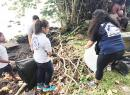 Students remove debris from along the shoreline of the Pala Lagoon