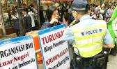 Hong Kong Police oversaw Indonesian domestic workers protesting against working conditions, agent fees in an organized demonstration in Causeway Bay, Hong Kong.  [Photo: Barry Markowitz]