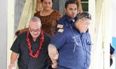 Deputy Commissioner Falana'ipupu Ta'ase Sagapolupele (left) and two other police officers escorting Police Officer Fa'auma Malo (right) from the DPS Central Station in Fagatogo, to an awaiting police unit, after he was arrested last Friday morning. Malo made his initial appearance Tuesday. [photo: courtesy]