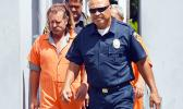 Dean J. Fletcher (left) is escorted by a police officer after his initial appearance in District Court yesterday. According to media reports, Fletcher is wanted by Tongan authorities for murder in the island Kingdom.  [photo: AF]