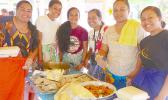 Array of yummy food with young ladies serving