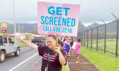 "Woman with ""get tested"" sign for Breast Cancer Awarenss Month"