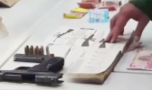 Iraqi money, illegal guns and ammunition, as well as a hardcover book with descriptions of various guns