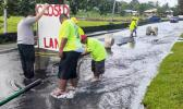 DPW crew installing lane closed sign where Fagaima road is flooded